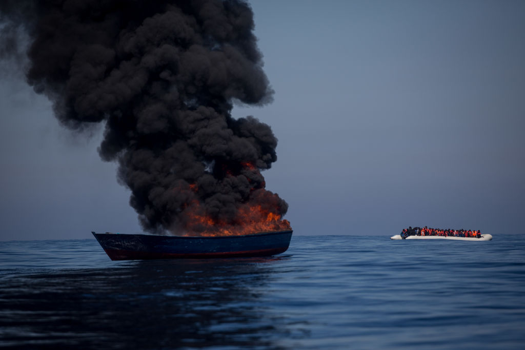 a boat owned by traffickers is torched after migrants transferred