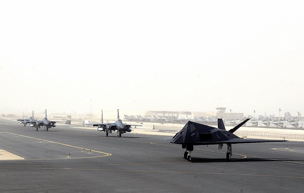 Pictured: An F-117 and F-15s prepare to launch from the U.S. Air Force base at Al Udeid, Qatar. (Image source: USAF/Wikimedia Commons)